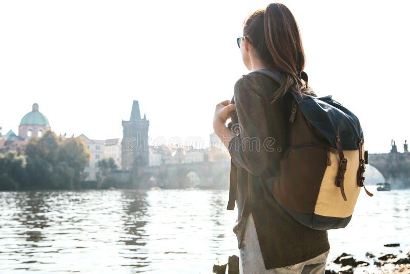 有背包的一个美丽的年轻旅游女孩在伏尔塔瓦河河旁边站立在布拉格并且敬佩其中一多数 库存图片