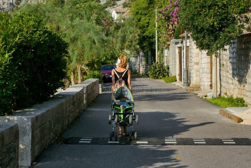 有背包的一名妇女走与一辆婴儿推车的在一度假胜地在黑山 库存照片