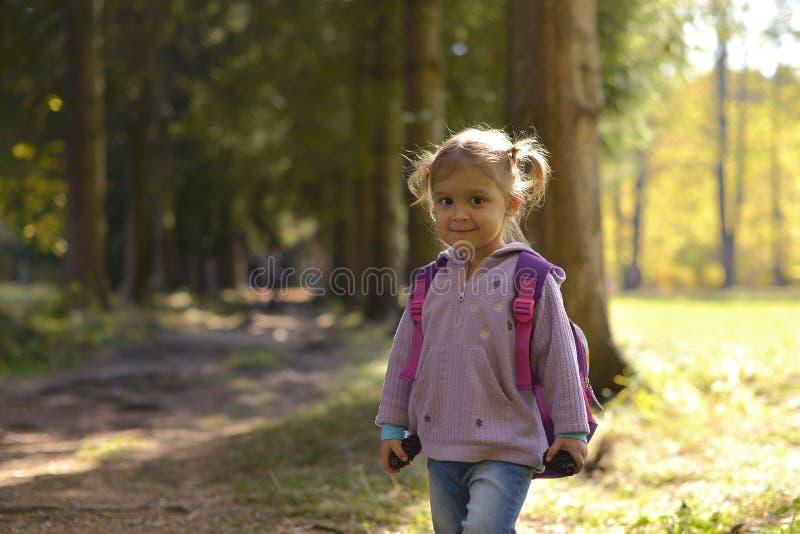 有背包的一女孩在森林公园和微笑站立 免版税库存照片