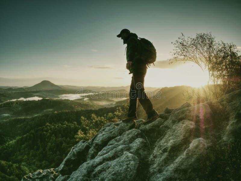 有背包的上升的远足者在山 峭壁登山人紧贴的岩石 图库摄影