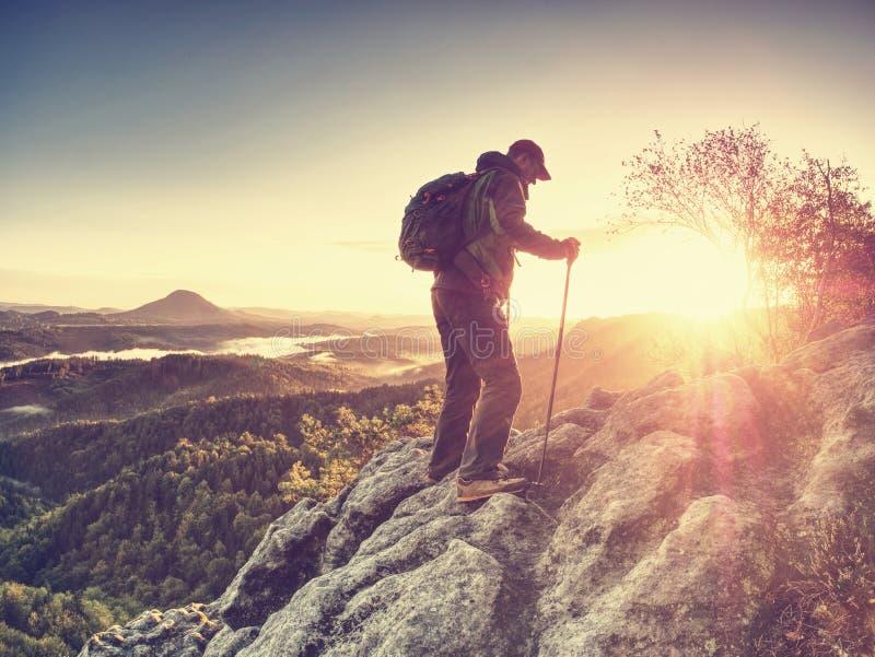 有背包的上升的远足者在山 峭壁登山人紧贴的岩石 免版税库存图片