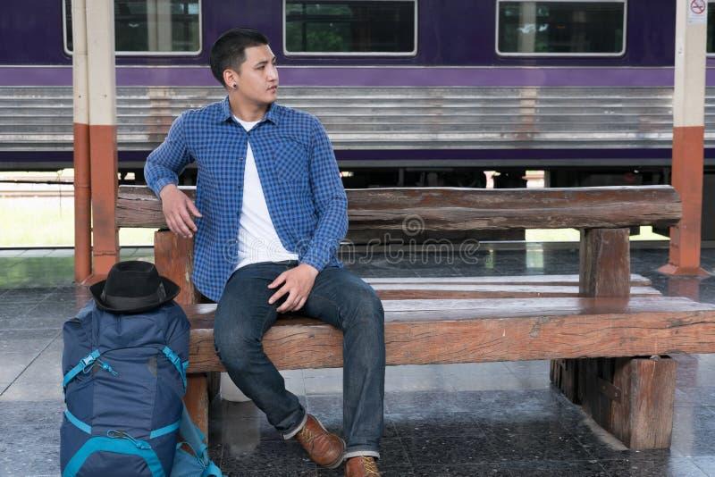 有背包的亚裔人坐平台在火车站 ba 免版税库存照片