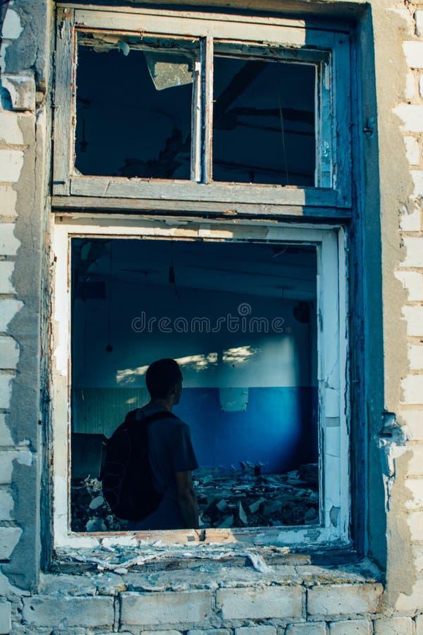 有背包的人在破坏毁坏了老修造的窗架 库存照片