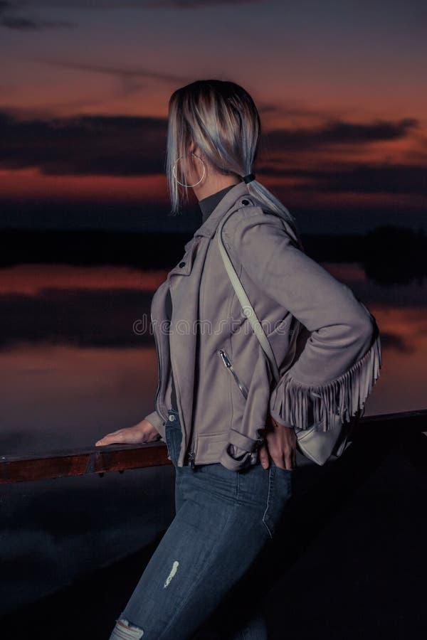 有背包的女孩在到木篱芭旁边站立在s 免版税库存照片
