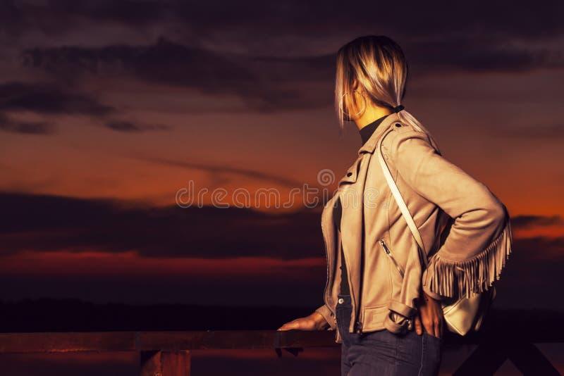 有背包的女孩在到木篱芭a旁边站立 库存图片