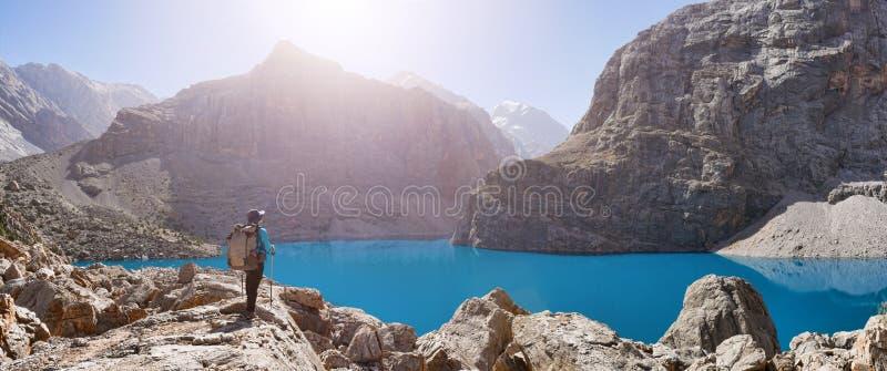 有背包的女孩在湖在落矶山脉backgroun的大Alo附近 免版税库存图片