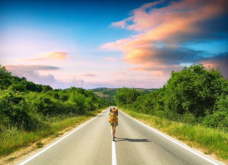 有背包的女孩徒步旅行者在山路 库存照片
