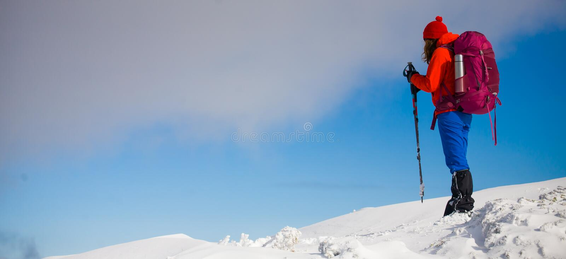 有背包的女孩走在山的雪的 图库摄影
