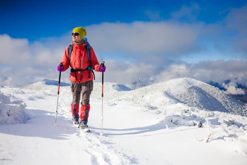 有背包的女孩走在山的雪的 免版税库存图片