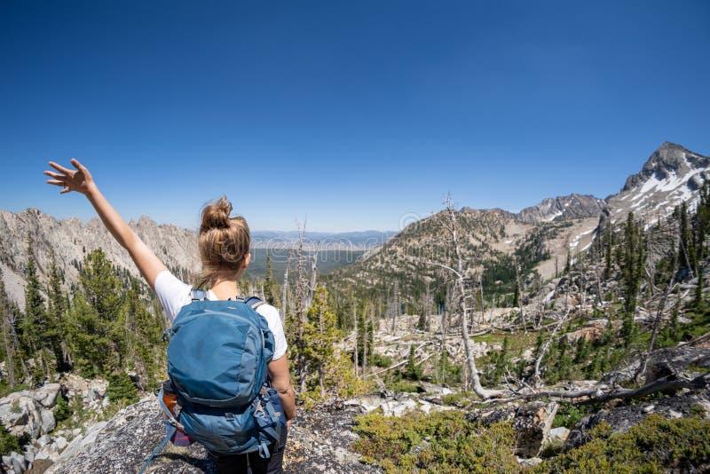 有背包的女性徒步旅行者沿Sawtooth湖足迹在爱达荷 后面饰面照相机 独奏女性旅行和远足的概念 免版税图库摄影