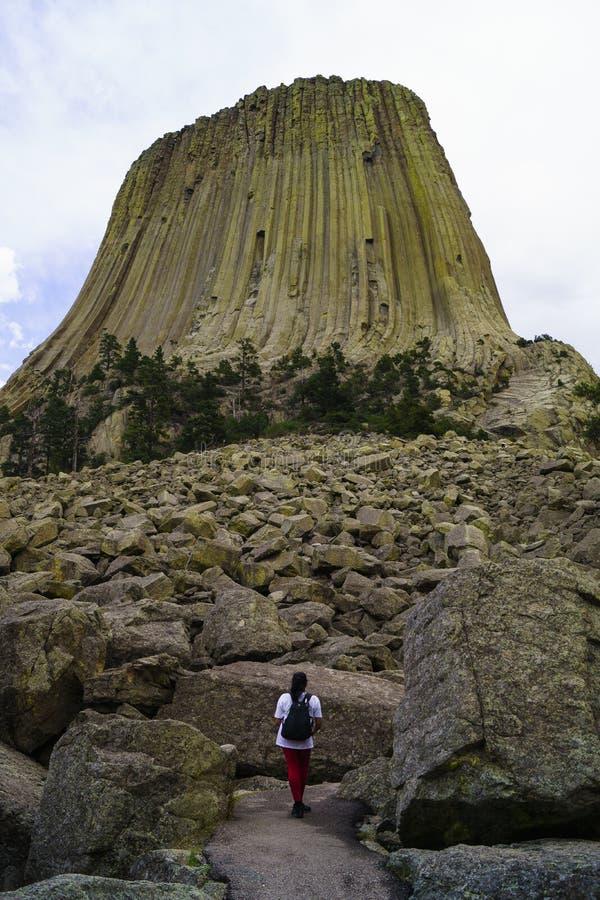 有背包的女性远足者在魔鬼塔基地在怀俄明 库存照片