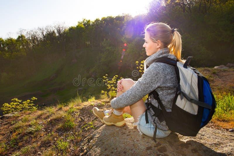有背包的妇女休假和在远足的享用视图  库存照片