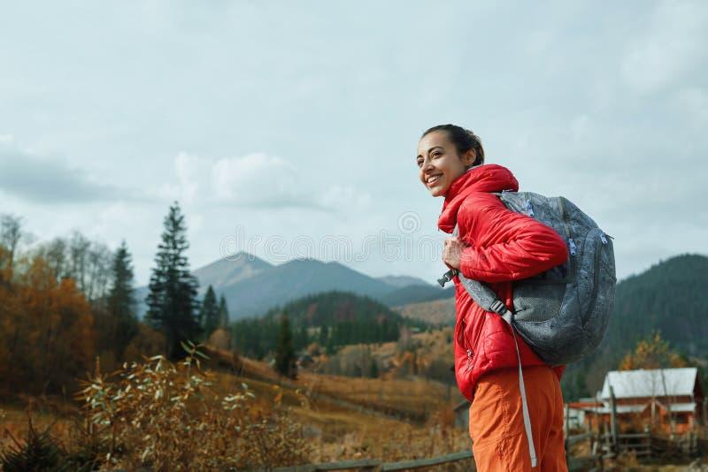 有背包的妇女徒步旅行者,佩带在红色夹克和橙色裤子,站立在山背景 库存照片
