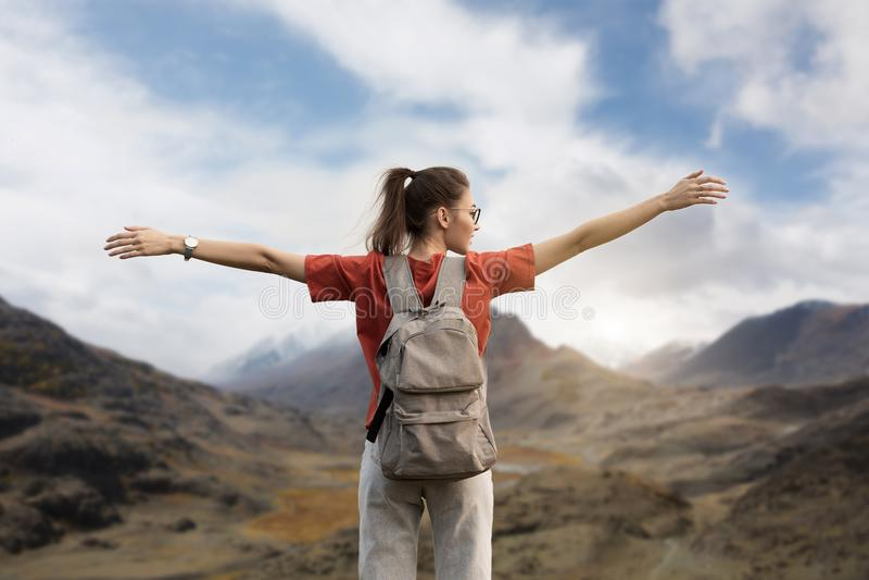 有背包的妇女旅客,举起她的手,在山的上面的立场 自然,多雪的山秀丽  免版税库存图片