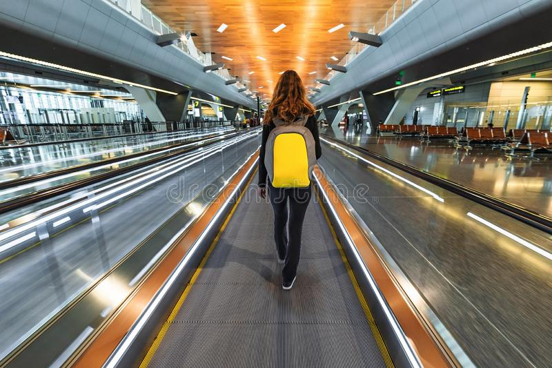 有背包的妇女旅行家在移动的走道travolator去在新的哈马德国际机场 回到视图 免版税库存图片
