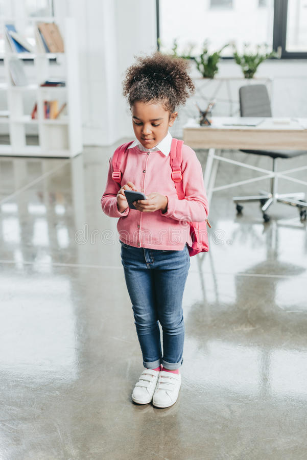 有背包的小女孩使用智能手机,当站立在现代办公室时 免版税库存图片