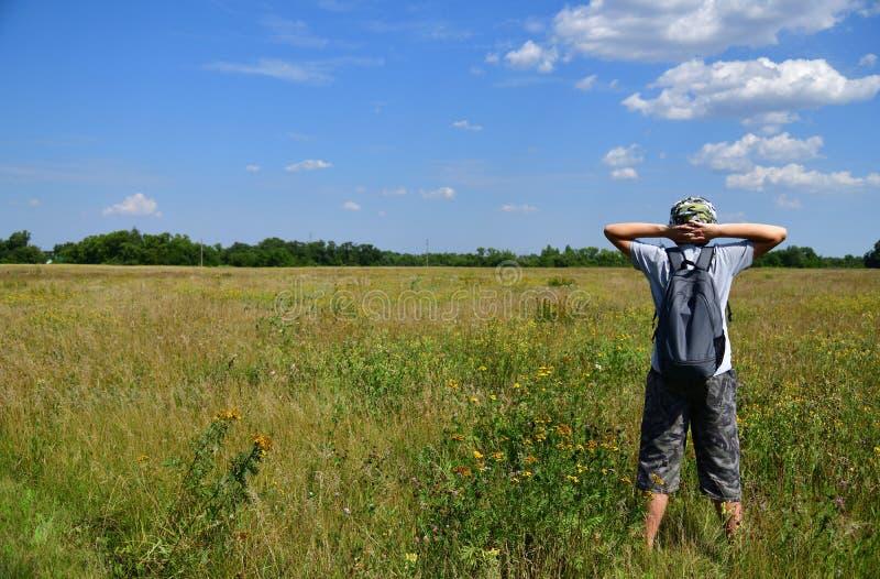有背包的少年在草甸站立 免版税库存图片