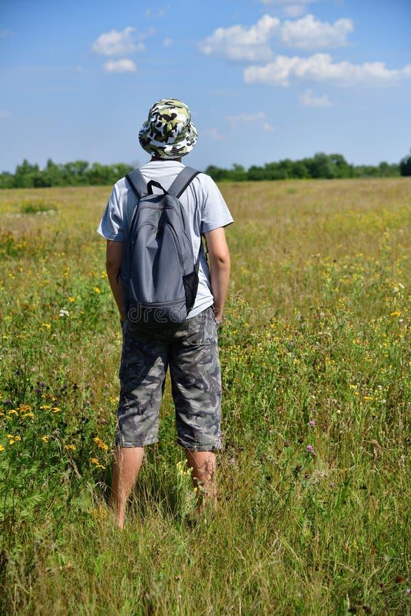 有背包的少年站立与他的在草甸的后面 库存照片