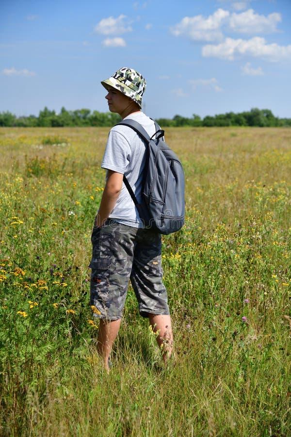 有背包的少年站立与他的在草甸的后面 免版税图库摄影
