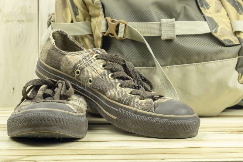 有背包的布朗运动鞋在木背景 库存照片