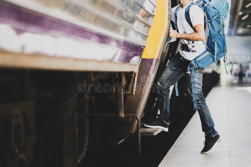 有背包的年轻亚裔旅客在铁路,举行和提高对有背包的一列火车的旅客旅途旅行的在 免版税库存照片