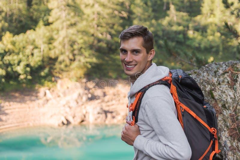 有背包的年轻人微笑对照相机的在远足旅途期间 库存图片