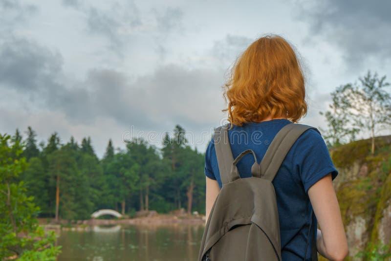 有背包的年轻俏丽的夫人走户外在夏天晚上的 美好的风景背景的游人 Monrepos公园, 免版税库存照片
