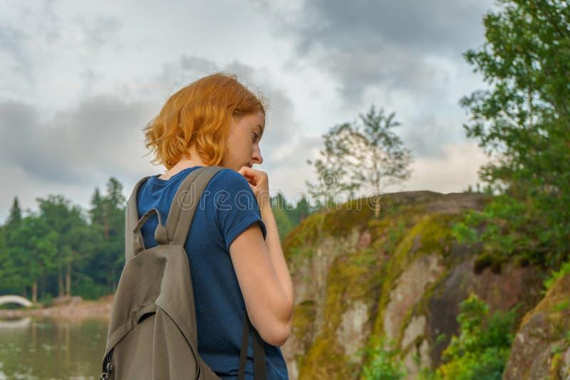 有背包的年轻俏丽的夫人走户外在夏天eveni的 免版税库存照片
