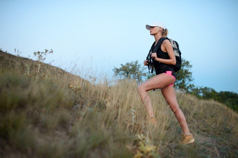 有背包的年轻十几岁的女孩享受在山的看法 总和 图库摄影