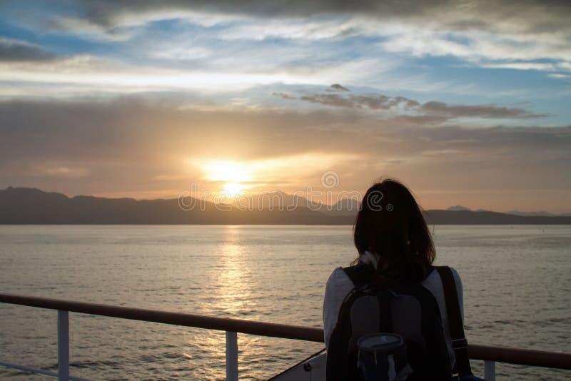 有背包的年轻女人女孩在肩膀射击从后面敬佩在撒丁岛沿海的日出用强烈的桔子 免版税库存图片