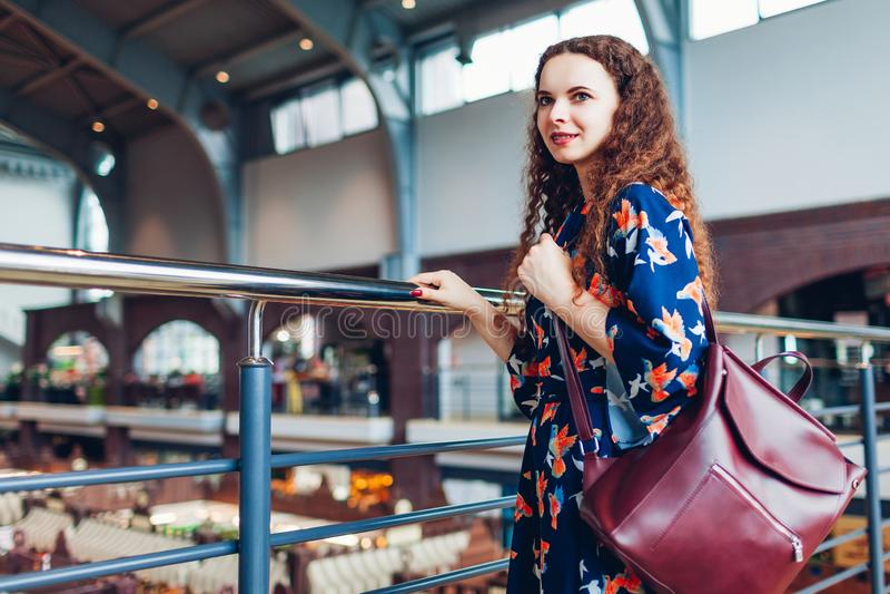 有背包的年轻女人走在购物中心窗口购物附近的 时兴的辅助部件 免版税库存图片