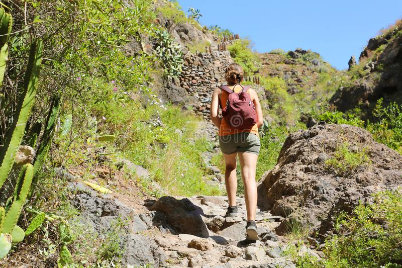 有背包的年轻徒步旅行者妇女攀登陡峭的岩石地形 免版税库存照片