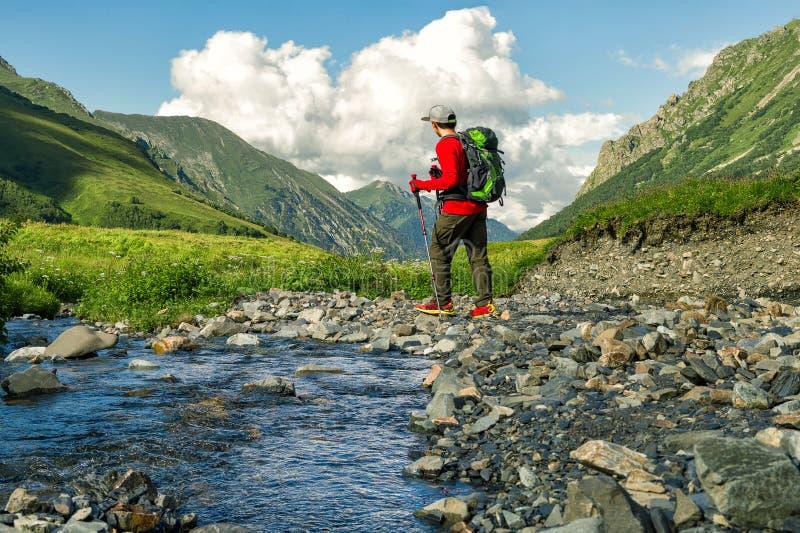 有背包的年轻活跃徒步旅行者在山背景 免版税库存图片