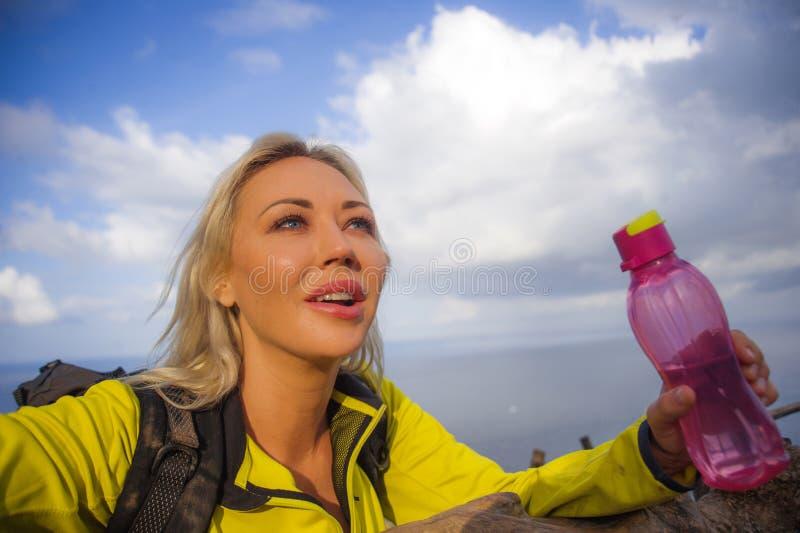 有背包的年轻美丽和愉快的徒步旅行者妇女远足在海山峭壁探索热带目的地的独奏享用 免版税图库摄影
