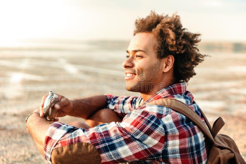 有背包的微笑的人喝从在海滩的熟悉内情的烧瓶的 免版税库存照片