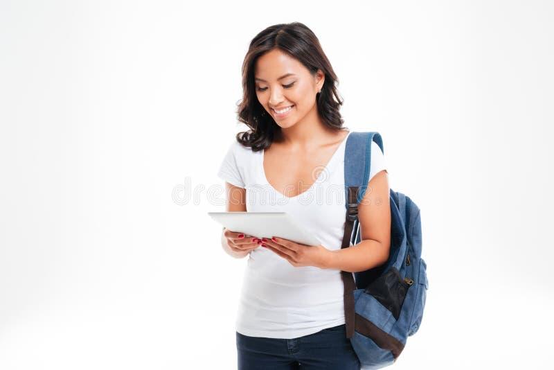 有背包的快乐的可爱的亚裔女孩使用片剂计算机 库存照片