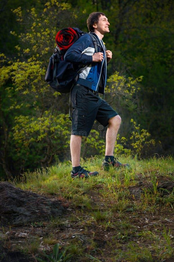有背包的快乐的年轻人享受步行的道路在s期间 库存照片
