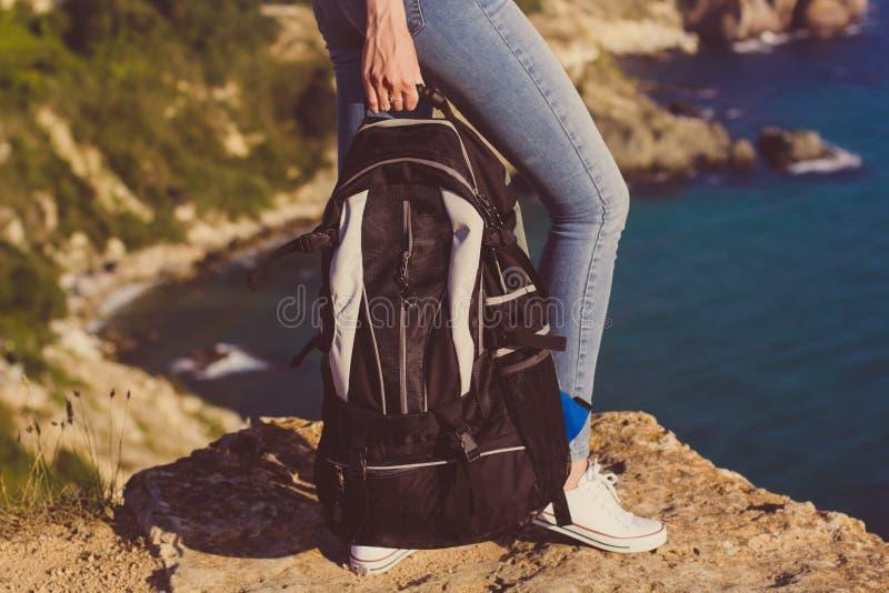 有背包的愉快的女孩在她的手上 免版税库存图片