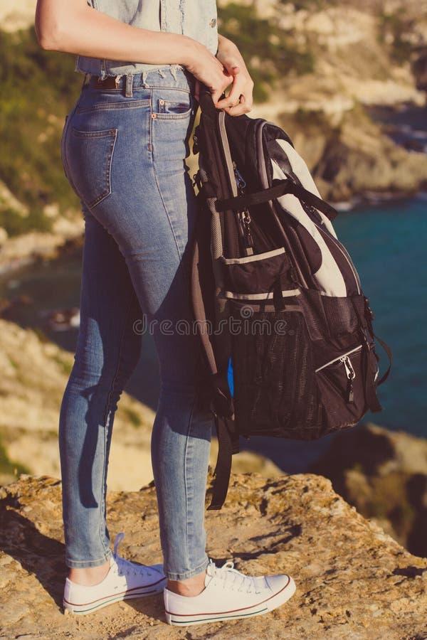 有背包的愉快的女孩在她的手上 图库摄影
