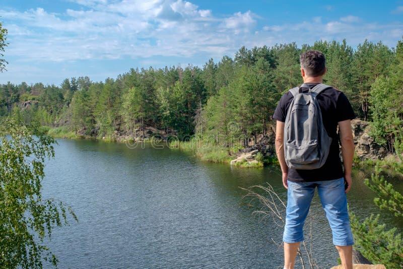 有背包的成人白游人在岩石站立
