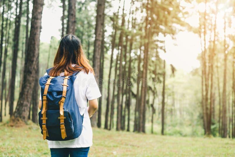 有背包的旅客亚裔妇女走在热带森林冒险旅行癖旅行人概念的道路的 免版税库存图片
