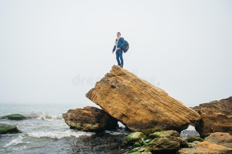 有背包的旅客在岩石站立反对有波浪的美丽的海,摆在安静附近的一个时髦的行家男孩 库存图片