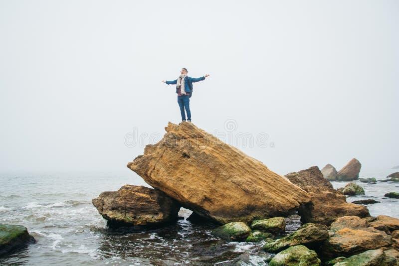 有背包的旅客在岩石站立反对有波浪的美丽的海,摆在安静附近的一个时髦的行家男孩 库存照片