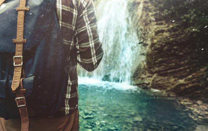 有背包的旅游人到达了他的在瀑布远足旅途旅行艰苦跋涉概念的背景特写镜头的和立场 免版税库存照片
