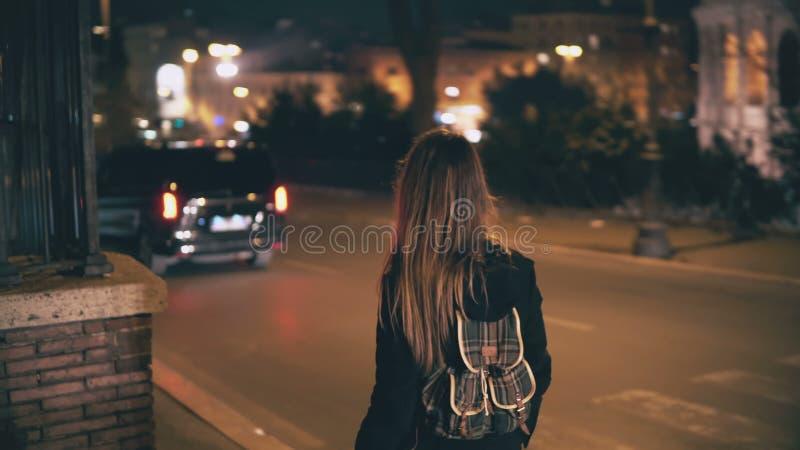 有背包的深色的妇女后走在晚上的 可爱的女孩审阅市中心在路附近在晚上 免版税库存图片