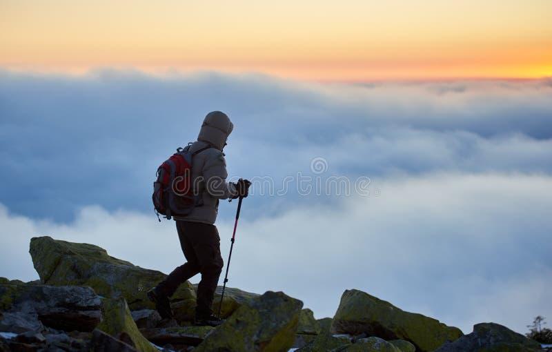 有背包的游人在有雾的谷和天空蔚蓝背景的落矶山脉在日出 库存图片