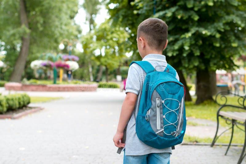 有背包的男孩在公园走 免版税库存照片