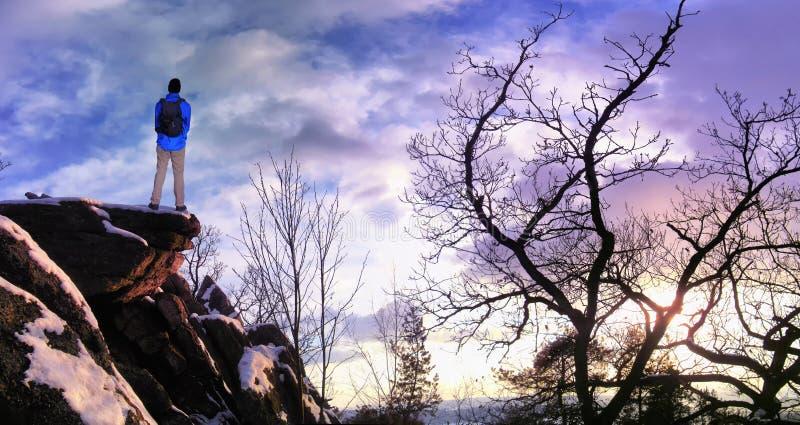有背包的男性徒步旅行者在城市后的山脉峭壁看坚固性冬天风景享受周末的 免版税库存照片