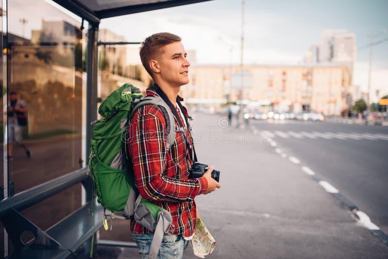 有背包的男性游人在公共汽车站 免版税图库摄影