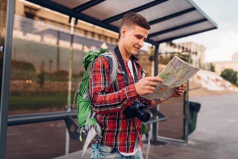 有背包的男性游人在公共汽车站 库存照片